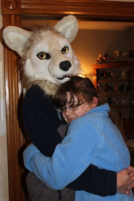 husband wearing unpainted fursuit wolf head hugging daughter